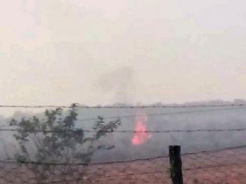 Incêndio em pastagem nos arredores da sede da fazenda, provocado durante invasão (Foto: Reprodução)