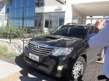 Carro deixa edifício com João Baird preso na manhã desta terça-feira (Foto: Izabela Sanchez)
