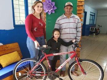 A pequena Sthefany ao lado de seu pai Denílson e a Secretaria da Agricultura Neyde Ramires, recebendo a bicicleta. Foto: Divulgação